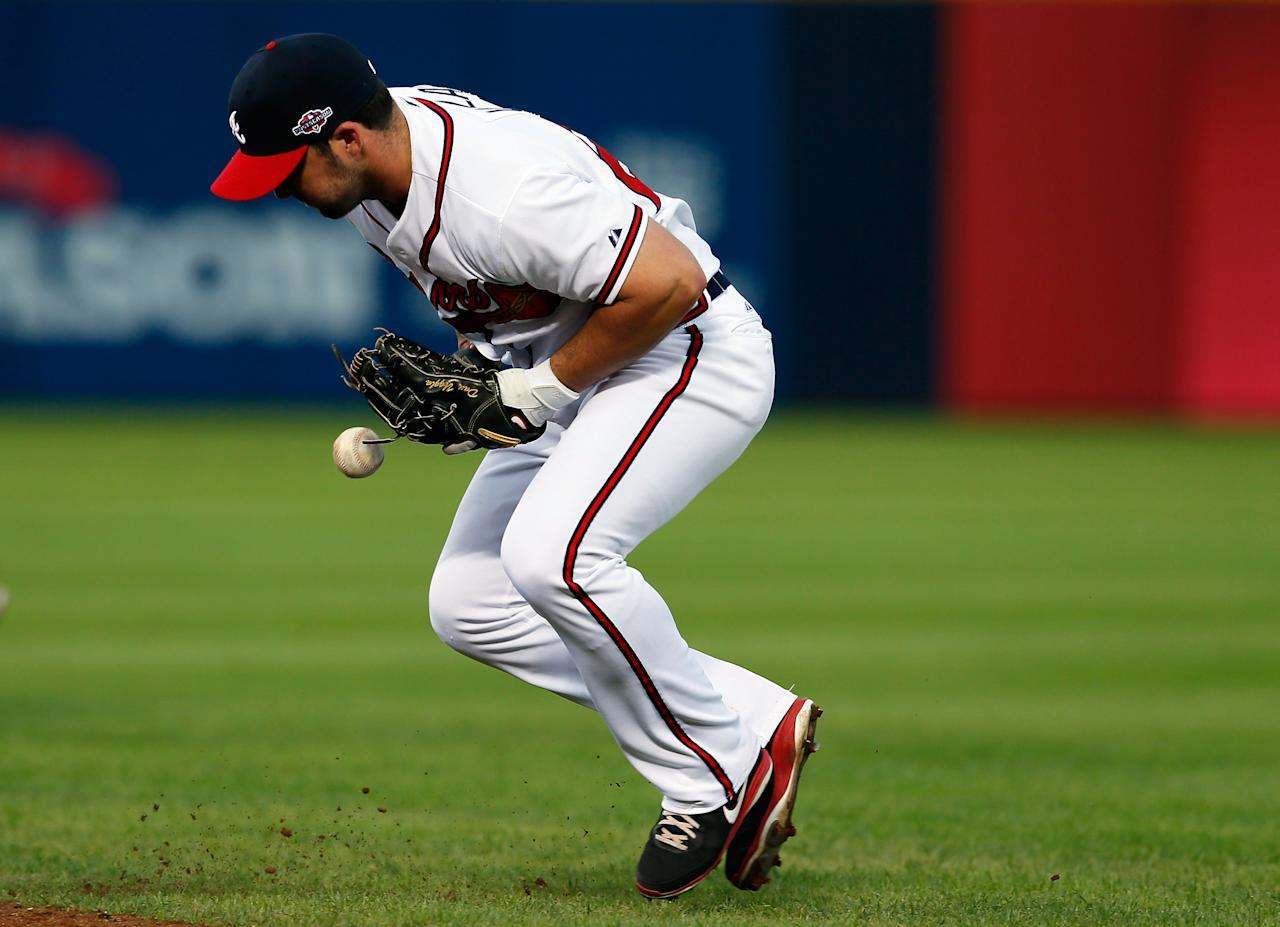 ATLANTA, GA - OCTOBER 05:  Dan Uggla #26 of the Atlanta Braves bobbles a groundball hit by David Freese #23 of the St. Louis Cardinals in the seventh inning during the National League Wild Card playoff game at Turner Field on October 5, 2012 in Atlanta, Georgia.  (Photo by Kevin C. Cox/Getty Images)