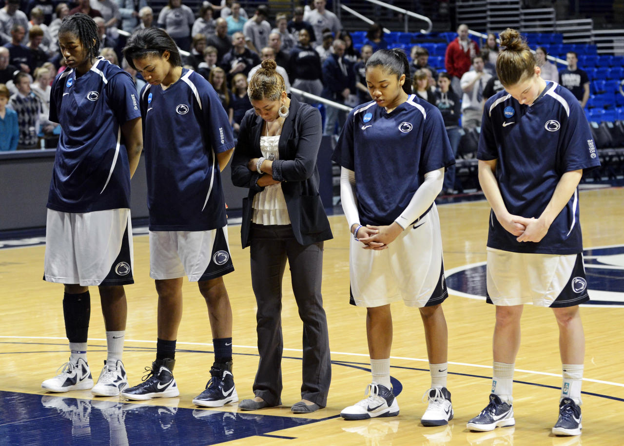 Members of the Penn State NCAA college basketball team pause for a moment of silence in honor of former Penn State football coach Joe Paterno before a game against Iowa, Sunday, Jan. 22, 2012, in State College, Pa. Paterno died Sunday at the age of 85. (AP Photo/John Beale)