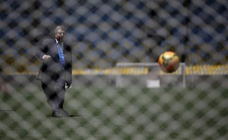 International Olympic Committee (IOC) President Thomas Bach kicks a soccer ball during a visit to Maracana stadium in Rio de Janeiro