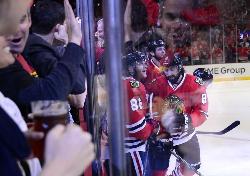 Fans pound on the glass as Blackhawks Nick Leddy delivers the first goal of the game during Game 2 of the Western Conference finals in the NHL hockey Stanley Cup playoffs Wednesday, May 21, 2014, in Chicago. The Kings won 6-2