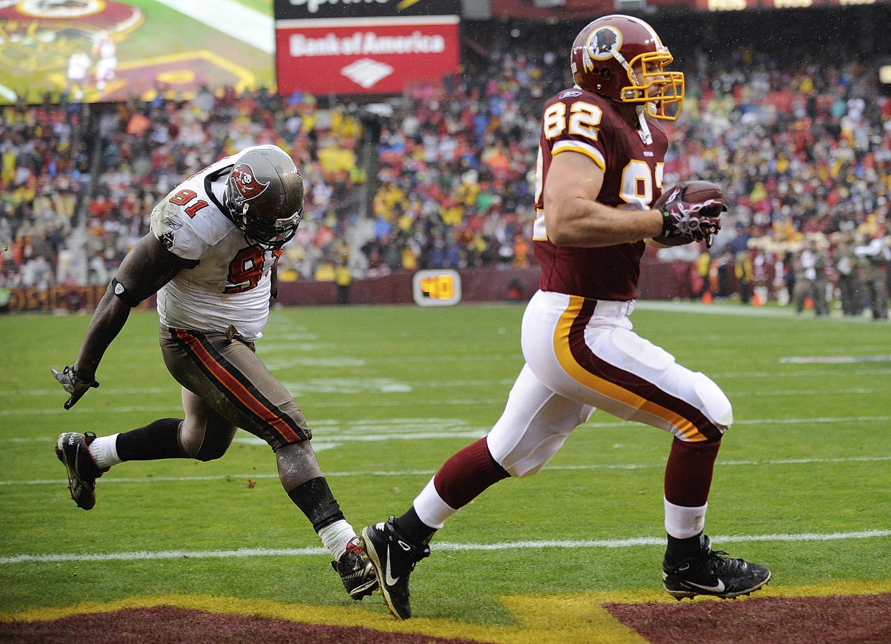 Washington Redskins tight end Logan Paulsen (82) carries the ball into the end zone for a touchdown as Tampa Bay Buccaneers defensive end Stylez White chases him during the first half of an NFL football game in Landover, Md., Sunday, Dec. 12, 2010.