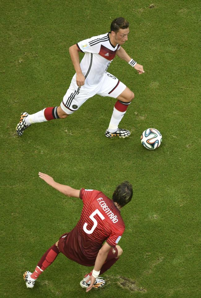 Germany's Mesut Ozil fights for the ball with Portugal's Fabio Coentrao during their 2014 World Cup Group G soccer match at the Fonte Nova arena in Salvador June 16, 2014. REUTERS/Francois Marit/Pool (BRAZIL - Tags: SOCCER SPORT WORLD CUP)