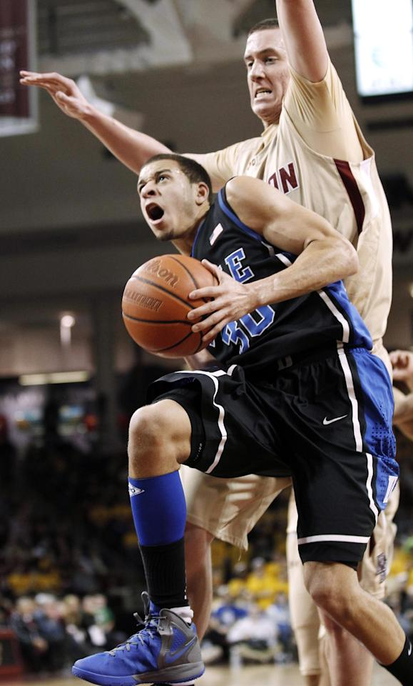 Duke's Seth Curry drives to the basket past Boston College's Dennis Clifford during the second half of Duke's 75-50 win in an NCAA college basketball game in Boston, Sunday, Feb. 19, 2012. (AP Photo/Winslow Townson)