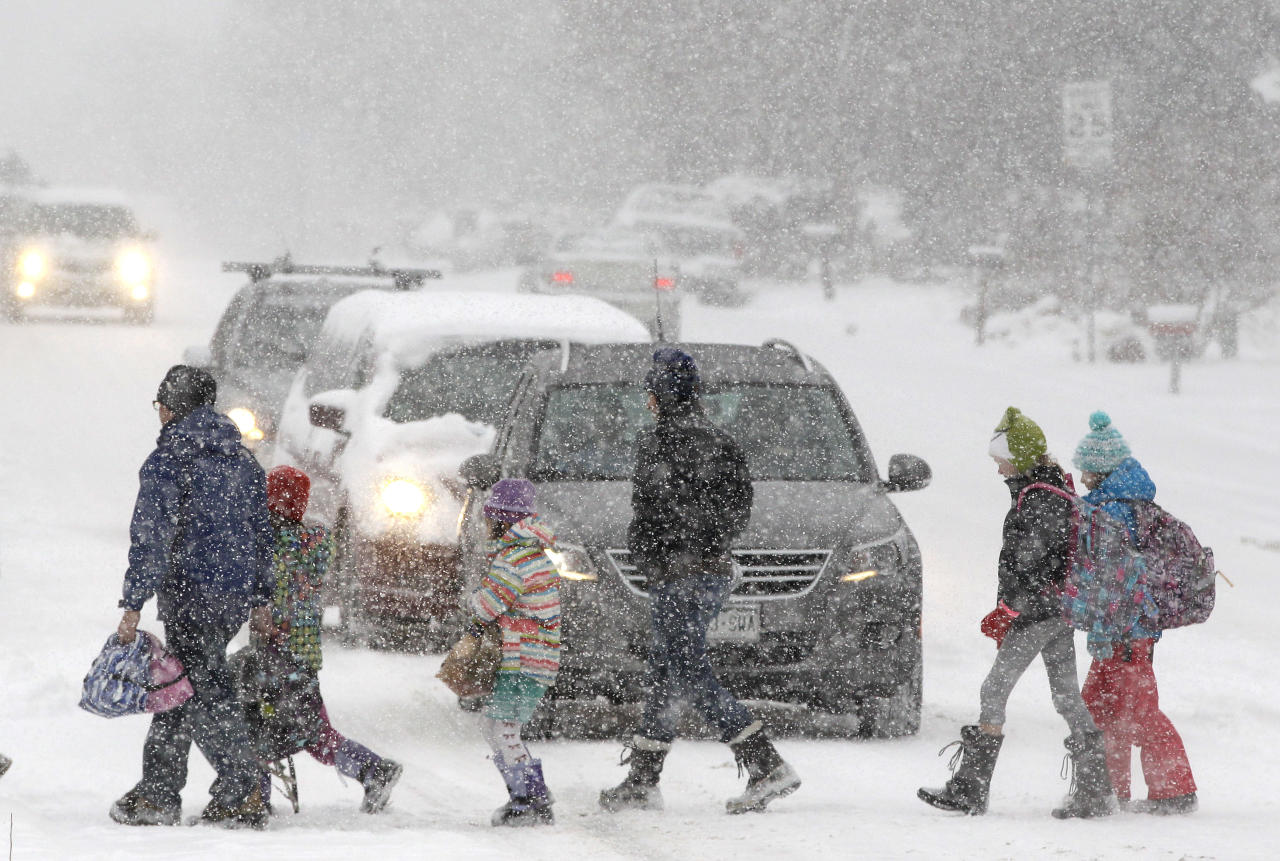 Elementary school students, some escorted by parents, cross a snowy street en route to school as a blizzard dropped snow over Boulder, Colo., Wednesday Dec. 19, 2012. A storm that has dumped more than a foot of snow in the Rocky Mountains is heading east and is forecast to bring the first major winter storm of the season to the central plains and Midwest. (AP Photo/Brennan Linsley)