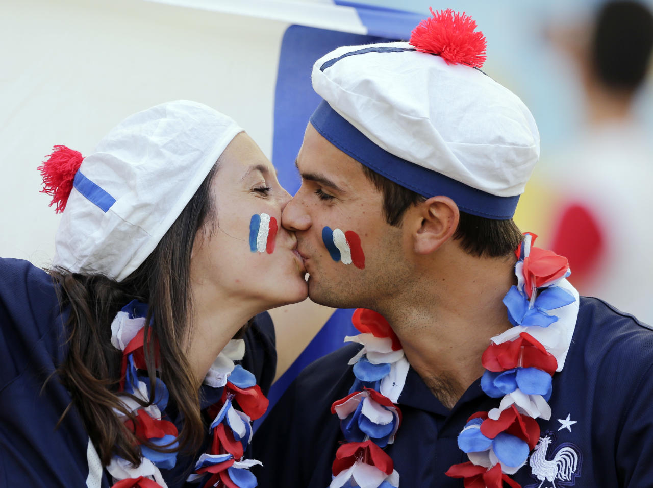 French soccer fans kiss before the World Cup quarterfinal soccer match between Germany and France at the Maracana Stadium in Rio de Janeiro, Brazil, Friday, July 4, 2014. (AP Photo/Matthias Schrader)