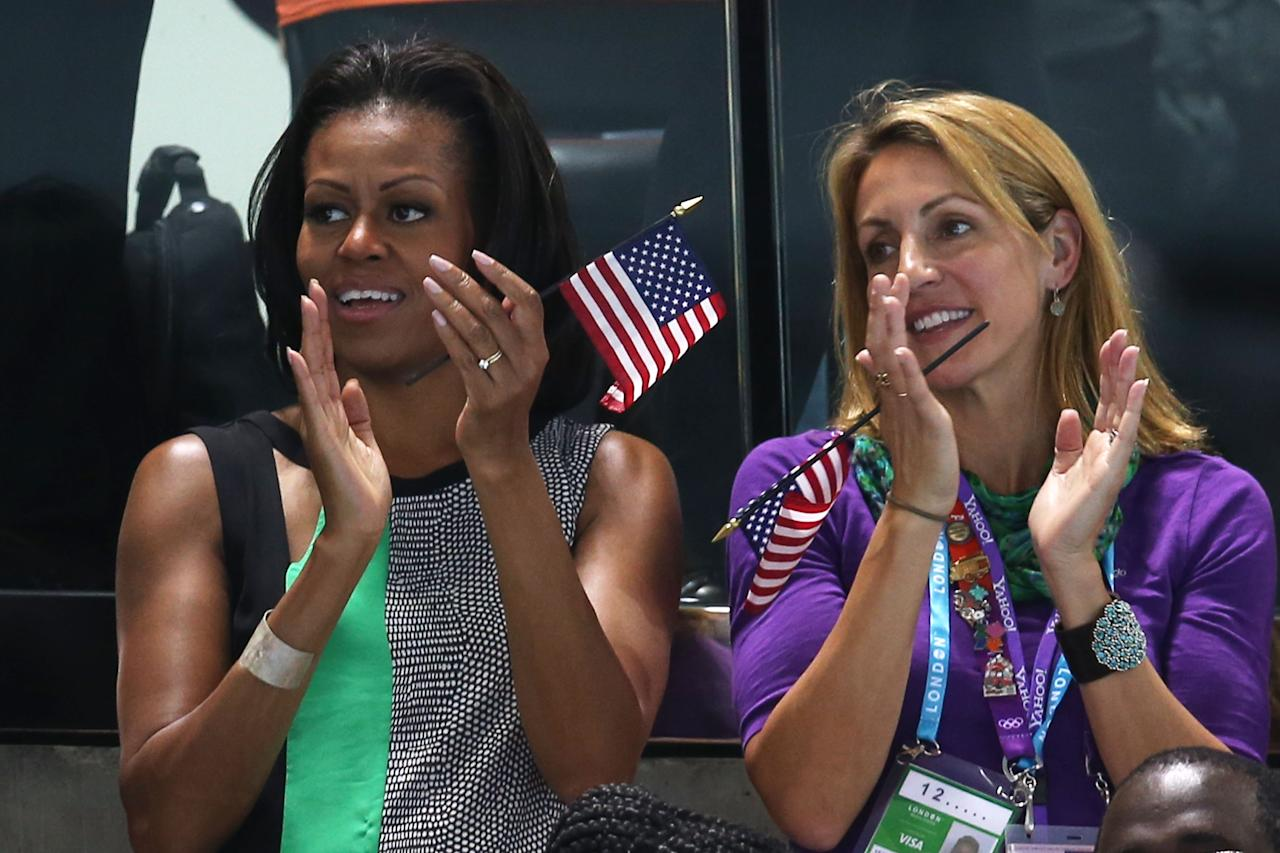 First Lady of the United States, Michelle Obama supports the USA Olympic Swim team along with Summer Sanders durng the evening session of the swimming  on Day 1 of the London 2012 Olympic Games at the Aquatics Centre on July 28, 2012 in London, England.  (Photo by Clive Rose/Getty Images)