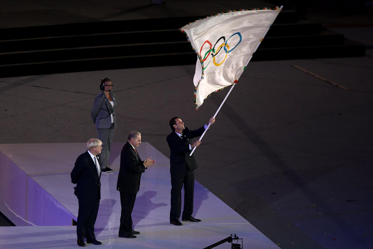 LONDON, ENGLAND - AUGUST 12:  The Olympic Flag is handed from Mayor of London, Boris Johnson to IOC President Jacques Rogge, who passes it to Mayor of Rio de Janeiro, Eduardo Paes during the Closing Ceremony on Day 16 of the London 2012 Olympic Games at Olympic Stadium on August 12, 2012 in London, England.  (Photo by Clive Brunskill/Getty Images)