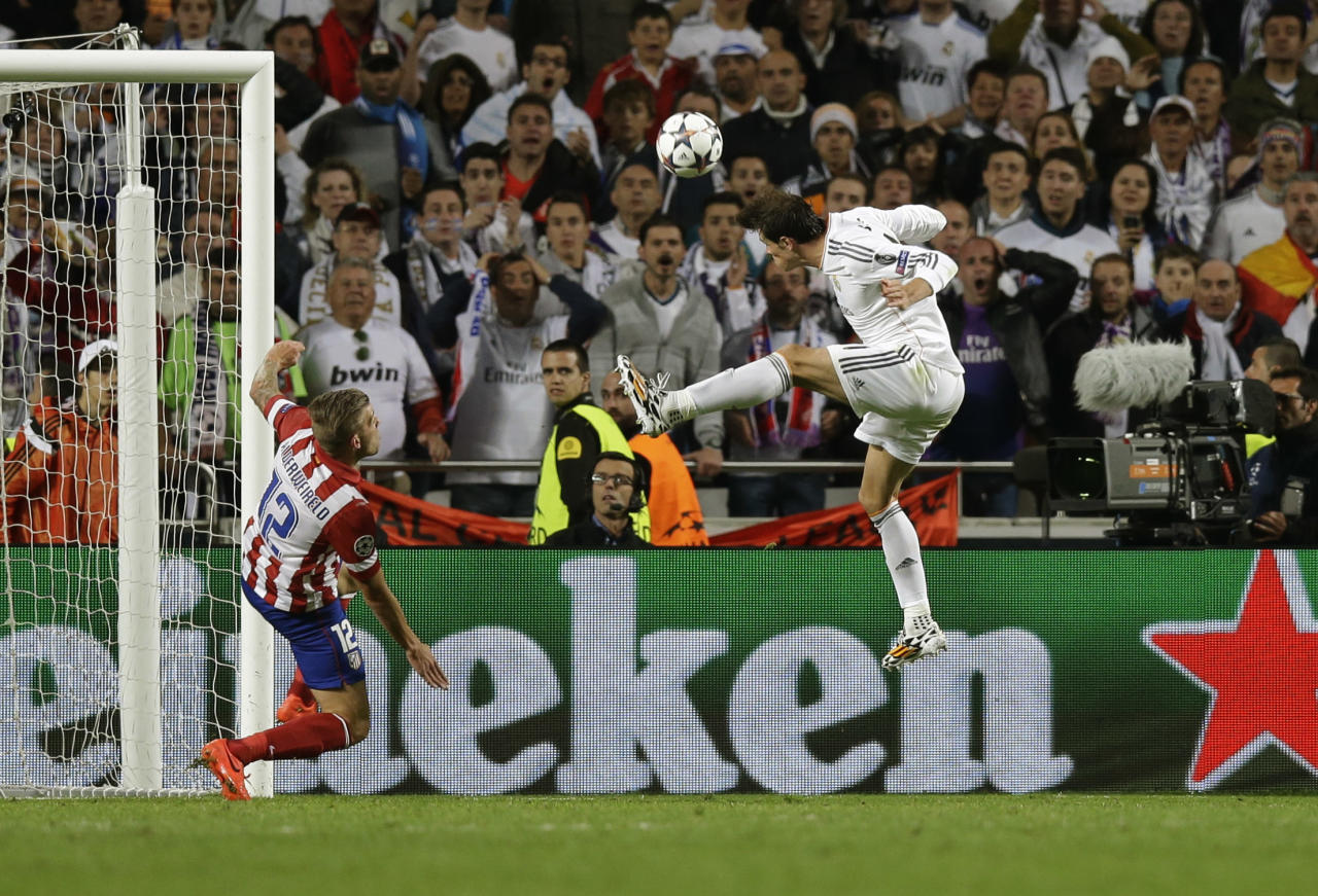 Real's Gareth Bale, right,  scores his side's 2nd goal, during the Champions League final soccer match between Atletico Madrid and Real Madrid in Lisbon, Portugal, Saturday, May 24, 2014. (AP Photo/Francisco Seco)