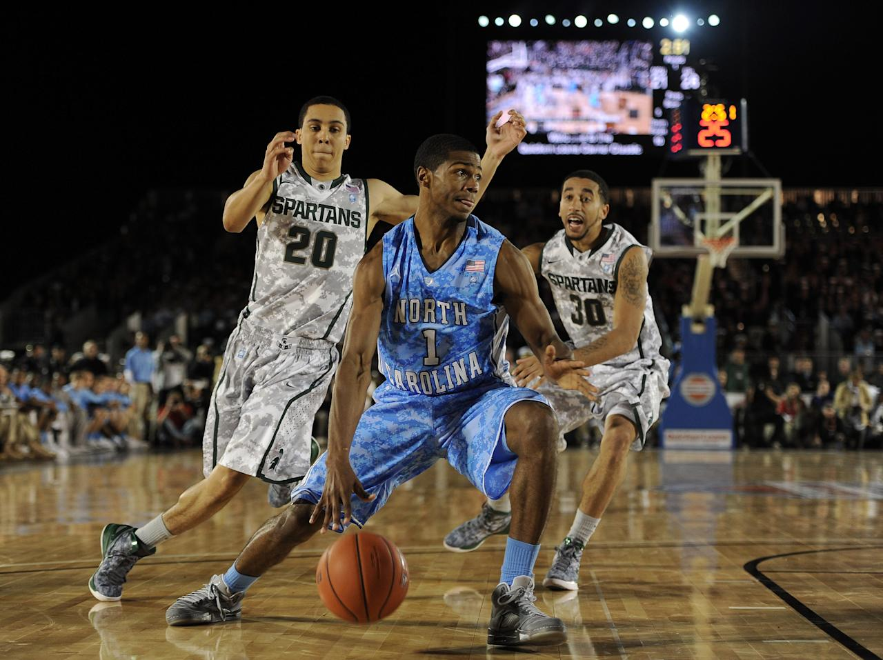 CORONADO, CA - NOVEMBER 11:  Dexter Strickland #1 of the North Carolina Tar Heels dribbles past Travis Trice #20 and Brandon Wood #30 of the Michigan State Spartans during the Quicken Loans Carrier Classic on board the USS Carl Vinson on November 11, 2011 in Coronado, California.  (Photo by Harry How/Getty Images)