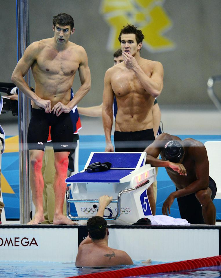 The United States men's swimming relay team, from left, Michael Phelps, Nathan Adrian, Cullen Jones and Ryan Lochte, below in water, react to their silver medal win in the men's 4x100-meter freestyle relay final at the Aquatics Centre in the Olympic Park during the 2012 Summer Olympics in London, Sunday, July 29, 2012. (AP Photo/The Canadian Press, Sean Kilpatrick)