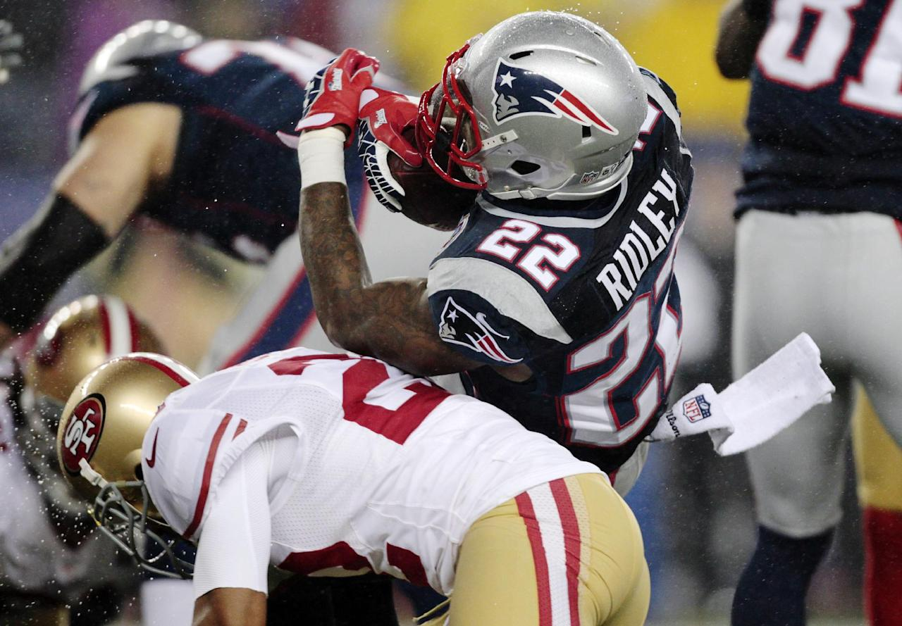San Francisco 49ers cornerback Carlos Rogers, bottom, hits New England Patriots running back Stevan Ridley (22) in the first quarter of an NFL football game in Foxborough, Mass., Sunday, Dec. 16, 2012. (AP Photo/Steven Senne)