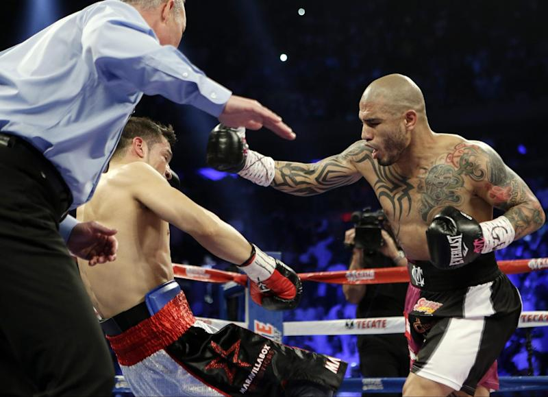 Miguel Cotto, of Puerto Rico, knocks down Sergio Martinez, of Argentina, during the first round of a WBC middleweight title boxing match Saturday, June 7, 2014, in New York