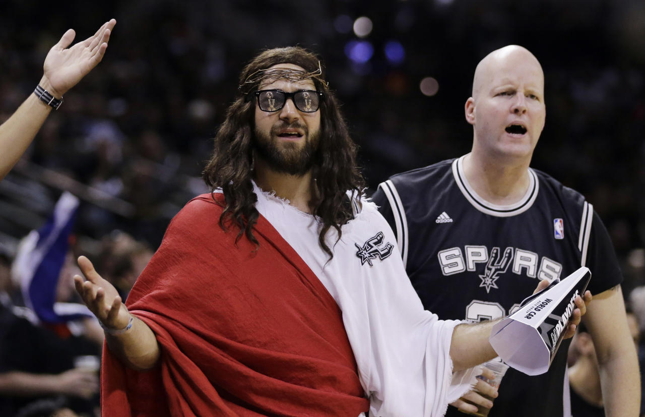 "Fans, including ""Spurs Jesus"", center, react to a call during the second half in Game 1 of the NBA basketball finals between the San Antonio Spurs and the Miami Heat on Thursday, June 5, 2014 in San Antonio. (AP Photo/Eric Gay)"