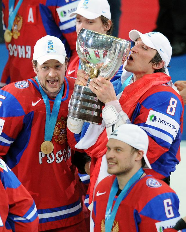 Russian Alexander Ovechkin kisses the trophy, as players celebrate after a final game of the IIHF International Ice Hockey World Championship in Helsinki on May 20, 2012, as Team Russia defeated team Slovakia 6-2 .   AFP PHOTO/ ALEXANDER NEMENOVALEXANDER NEMENOV/AFP/GettyImages