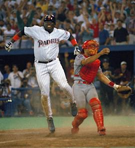 Tony Gwynn leaps in the air after sliding home safely to score the winning run in the 1994 MLB All-Star Game. (AP)