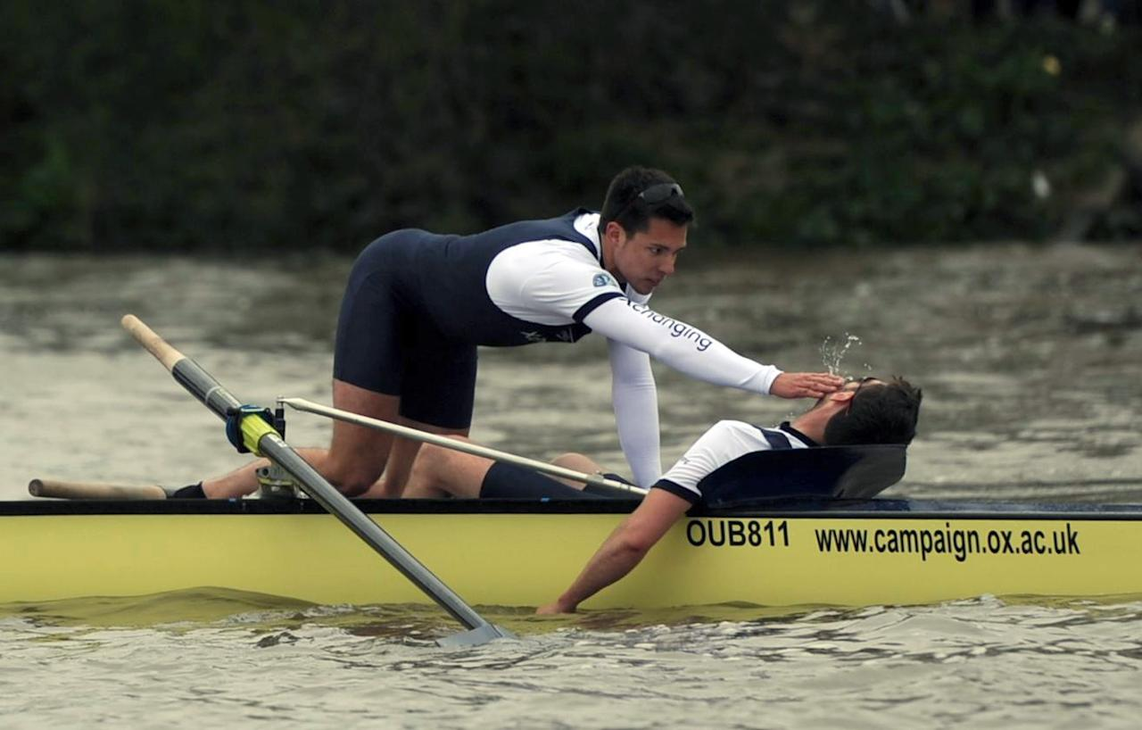 Oxford's Dr Alexander Wood, right, is assisted by a member of his crew after appearing to collapse following the 158th Boat Race on the river Thames, London, Saturday April 7, 2012. Cambridge won a dramatic Boat Race against Oxford on Saturday following a 31-minute mid-race postponement after a man jumped into the River Thames and swam between the crews. When the race was restarted halfway along the course, Oxford's German rower Dr. Hanno Wienhausen lost half of his oar after the crews clashed allowing Cambridge to cruise to victory up against effectively seven opponents. A margin of victory wasn't given by officials. (AP Photo/PA, Anthony Devlin) UNITED KINGDOM OUT