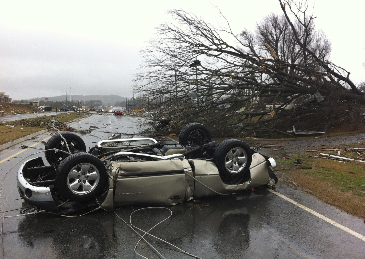 A vehicle lies on a road after a tornado moved through Adairsville, Ga. on Wednesday, Jan. 30, 2013. A fierce storm system that roared across northwest Georgia has left at least one person dead and a trail of damage that included demolished buildings in downtown Adairsville and vehicles overturned on Interstate 75 northwest of Atlanta. (AP Photo/David Goldman)