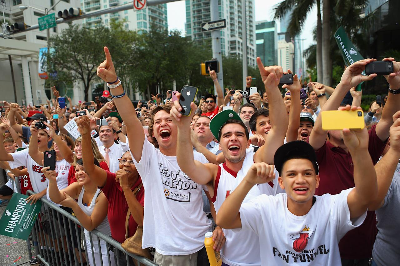 MIAMI, FL - JUNE 25:  Fans cheer as Miami Heat players pass by in a victory parade through the streets during a celebration for the 2012 NBA Champion Miami Heat on June 25, 2012 in Miami, Florida. The Heat beat the Oklahoma Thunder to win the NBA title.  (Photo by Joe Raedle/Getty Images)
