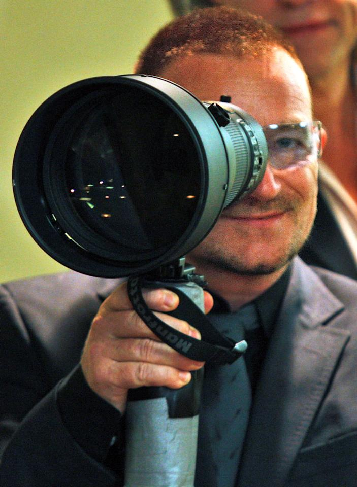 Musician Bono looks through a photographer's telephoto lens while waiting to meet with Japanese Prime Minister Taro Aso at a private meeting at the United Nations, Thursday, Sept. 25, 2008.  (AP Photo/Kathy Willens)