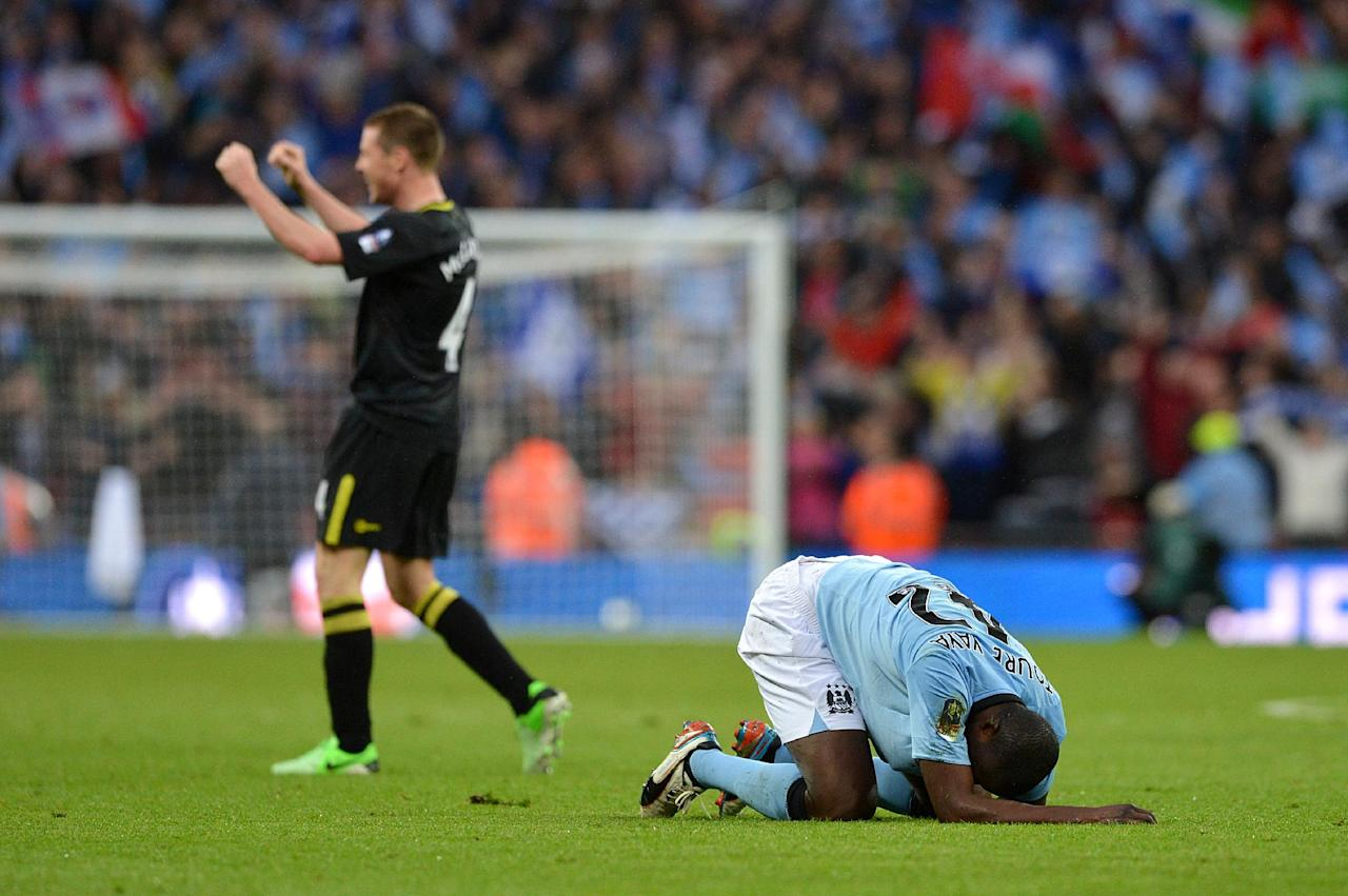 Manchester City's Yaya Toure (right) is left dejected on the floor as Wigan Athletic's James McCarthy celebrates their victory, after the final whistle