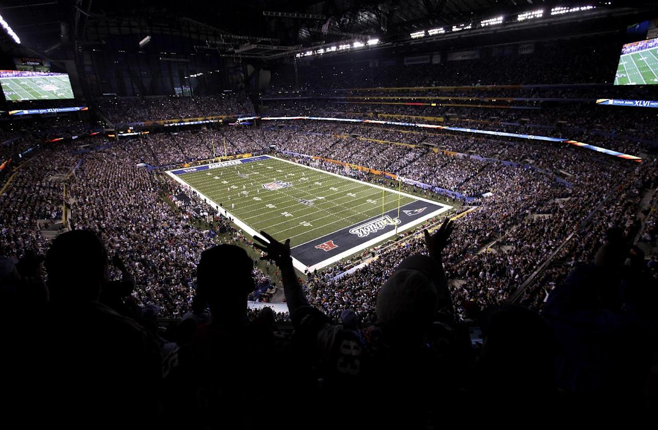 Football fans cheer during the first half of the NFL Super Bowl XLVI football game between the New York Giants and the New England Patriots on Sunday, Feb. 5, 2012, in Indianapolis. (AP Photo/Jae C. Hong)