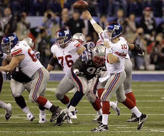 New York Giants quarterback Eli Manning throws a pass as New England Patriots defensive lineman Gerard Warren rushes during the second half of the NFL Super Bowl XLVI football game, Sunday, Feb. 5, 2012, in Indianapolis. (AP Photo/Michael Conroy)
