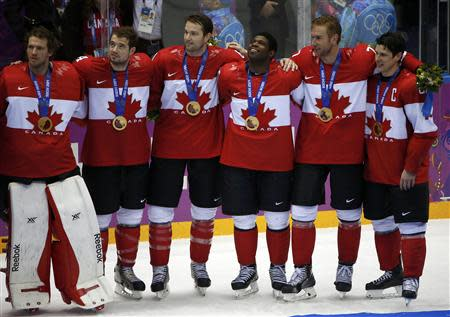 Canadian players pose during the medal presentation ceremony after their team defeated Sweden in the men's ice hockey final game at the 2014 Sochi Winter Olympic Games