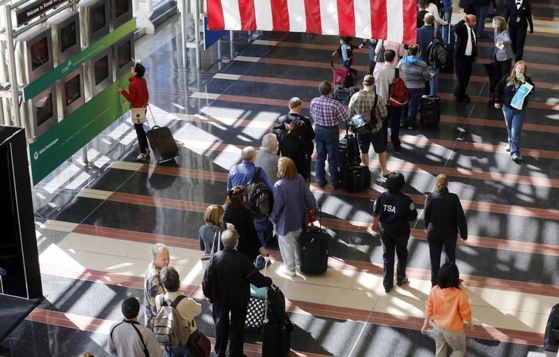 A line of passengers wait to enter the security checkpoint before boarding their aircraft at Reagan National Airport in Washington
