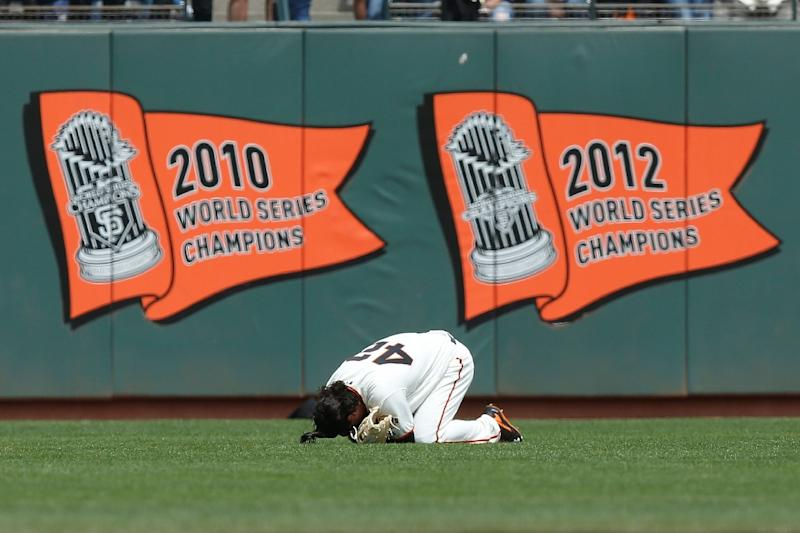 Jarrett Parker of the San Francisco Giants falls to the ground after making a catch against the outfield wall in the fourth inning against the Colorado Rockies at AT&T Park on April 15, 2017