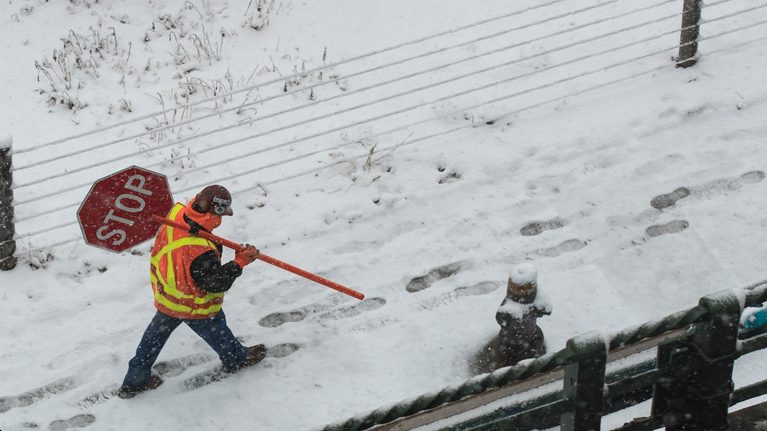 Construction Worker Carries Stop Sign In The Snow Near Brooklyn Bridge Park And Borough Of New York City