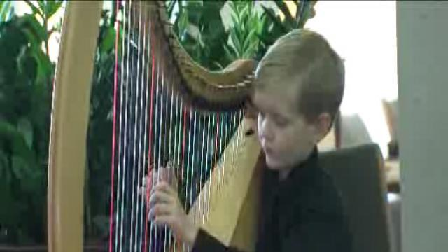 Boy harpist plays as mom gets treatment
