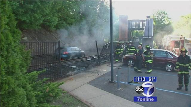 Car crashes onto Metro-North tracks, bursts into flames