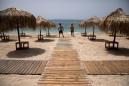 Greeks return to beaches in heatwave, but keep umbrellas apart